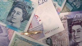 Cámara lenta de los billetes de banco de la libra esterlina de Reino Unido de la moneda de Bitcoin que gira metrajes