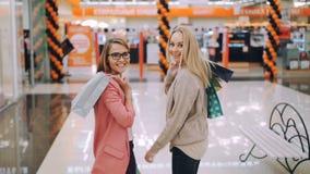 Cámara lenta de los clientes felices alegres de las señoras jovenes que caminan junto en el centro comercial entonces que sostien metrajes