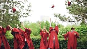 Cámara lenta de los estudiantes alegres que lanzan birretes en aire y que los cogen, riendo y disfrutando de día de graduación almacen de video