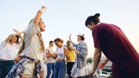 Cámara lenta de los estudiantes felices que van de fiesta en el baile del tejado y que ríen llevando a cabo bebidas mientras que  almacen de metraje de vídeo