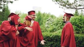 Cámara lenta de los estudiantes de graduación alegres de las muchachas y de los individuos que abrazan y que sacuden las manos qu metrajes