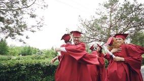 Cámara lenta de los estudiantes de graduación de los amigos que hacen el alto cinco y que se abrazan casquillos y vestidos del bi metrajes