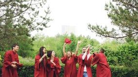 Cámara lenta de los graduados felices que lanzan birretes en aire, riendo y celebrando la graduación en campus de la universidad almacen de video