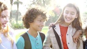 Cámara lenta de los niños que cuelgan hacia fuera en parque junto metrajes