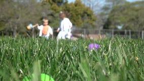 Cámara lenta de los niños que se divierten que recolecta los huevos en la caza de Pascua almacen de metraje de vídeo