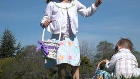 Cámara lenta de los niños que se divierten que recolecta los huevos en la caza de Pascua metrajes