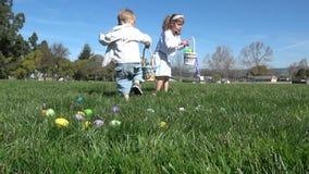 Cámara lenta de los niños que se divierten que recolecta los huevos en la caza de Pascua almacen de video
