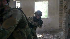 Cámara lenta de los soldados armados que corren adelante para atacar y para eliminar la blanco del terrorista en el edificio metrajes