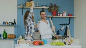A cámara lenta de pares alegres jovenes tenga el baile de la diversión y canto mientras que cocina en la cocina en casa