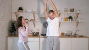 A cámara lenta de pares alegres jovenes tenga el baile de la diversión y canto mientras que cocina en la cocina en casa metrajes
