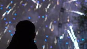 A cámara lenta de silueta del primer de los fuegos artificiales de observación del hombre solo en la celebración del Año Nuevo al metrajes