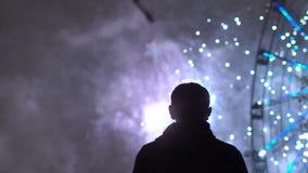 A cámara lenta de silueta del primer de los fuegos artificiales de observación del hombre solo en la celebración del Año Nuevo al almacen de video
