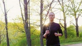 Cámara lenta de Steadicam tirada: Mujer joven que corre en la vida y el deporte sanos del bosque almacen de metraje de vídeo