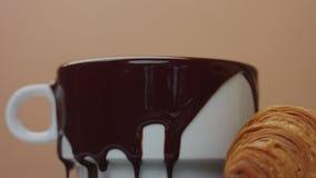 A cámara lenta de toma del chocolate caliente fuera de la taza que hace smooges agradables almacen de video