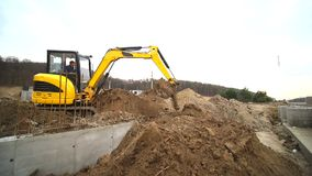 Cámara lenta de un cavador que cava un hoyo y que lanza la suciedad Primer de un cubo del excavador que lanza hacia fuera la tier almacen de metraje de vídeo