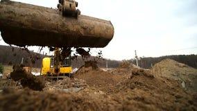 Cámara lenta de un cavador que cava un hoyo y que lanza la suciedad Primer de un cubo del excavador que lanza hacia fuera la tier almacen de video