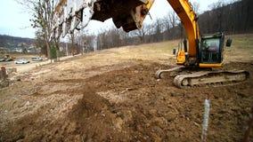 Cámara lenta de un cavador que cava un hoyo y que lanza la suciedad Primer de un cubo del excavador que lanza hacia fuera la tier metrajes