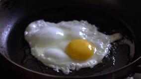 Cámara lenta de un huevo frito cocinado en el sartén para la comida de desayuno temprana almacen de video