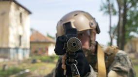 Cámara lenta de un soldado joven en un ajuste de la armadura y del casco en la posición para apuntar la blanco que se prepara par almacen de video
