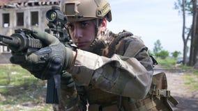 Cámara lenta de un soldado marino que está apuntando el arma a la blanco enemiga en un área del conflicto almacen de video