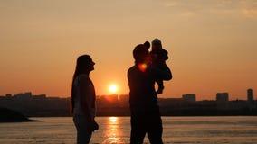 Cámara lenta de una familia joven que se divierte por el río en la puesta del sol almacen de metraje de vídeo