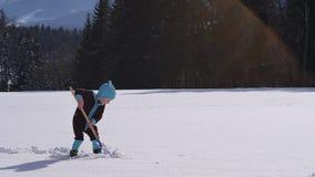 Cámara lenta de una nieve que lanza de la niña con una pala de la nieve almacen de video