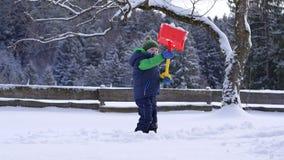 Cámara lenta de una nieve que lanza del niño pequeño con una pala de la nieve almacen de video
