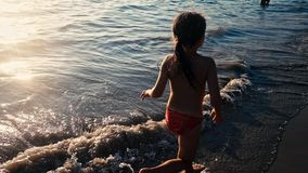 Cámara lenta de una pequeña muchacha descalza que corre en la arena mojada a lo largo del mar en la luz caliente de igualar el so almacen de video