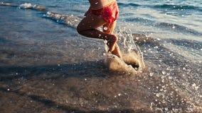 Cámara lenta de una pequeña muchacha descalza que corre en la arena mojada a lo largo del mar en la luz caliente de igualar el so almacen de metraje de vídeo