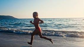 Cámara lenta de una pequeña muchacha descalza que corre en la arena mojada a lo largo del mar en la luz caliente de igualar el so metrajes
