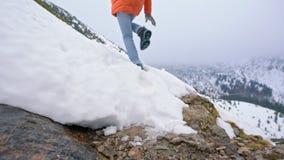 Cámara lenta de una señora Wading una corriente y un salto de la montaña por encima de la superficie en invierno almacen de metraje de vídeo
