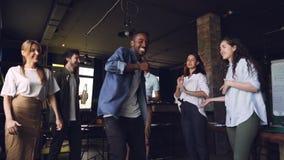 Cámara lenta del baile afroamericano emocionado del hombre en el partido corporativo en oficina con los colegas que llevan a cabo almacen de video