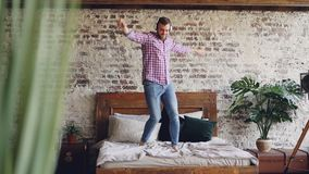 Cámara lenta del baile barbudo joven del hombre en cama matrimonial y de escuchar la música en auriculares Apartamento moderno de almacen de metraje de vídeo