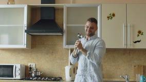 Cámara lenta del baile divertido joven atractivo del hombre y canto con la cucharón mientras que cocina en la cocina en casa almacen de metraje de vídeo