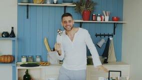 Cámara lenta del baile divertido joven atractivo del hombre y canto con la cucharón mientras que cocina en la cocina en casa almacen de video