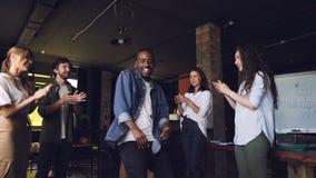 Cámara lenta del baile feliz del hombre joven de African American del propietario de negocio en el partido corporativo con los em metrajes