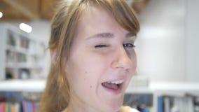 Cámara lenta del cierre para arriba de guiñar la cara del ojo de la muchacha sonriente almacen de metraje de vídeo
