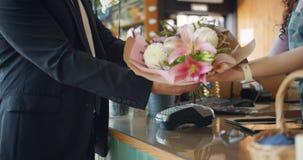 Cámara lenta del cliente que paga con la tarjeta de banco entonces que toma el ramo de flores metrajes
