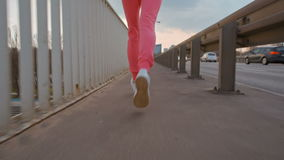 A cámara lenta del corredor de la muchacha que activa en el puente en la ciudad - opinión trasera del primer metrajes