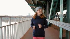 A cámara lenta del corredor femenino joven que activa sobre el puente industrial almacen de video