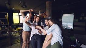 Cámara lenta del equipo multi-étnico que toma el selfie con las bebidas en el partido corporativo usando smartphone Los hombres y almacen de metraje de vídeo