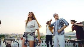 Cámara lenta del grupo multi-étnico de amigos que bailan y que se relajan en el partido al aire libre con DJ que usa el equipo pr almacen de metraje de vídeo