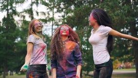 Cámara lenta del grupo multi-étnico de las muchachas alegres que baila el polvo de la pintura entonces que lanza en el partido al almacen de metraje de vídeo