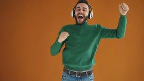 C?mara lenta del hombre joven barbudo que escucha la m?sica a trav?s de los auriculares y que baila divirti?ndose que disfruta de almacen de video