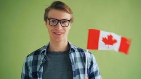 Cámara lenta del individuo hermoso en los vidrios que sostienen la bandera nacional de Canadá almacen de metraje de vídeo