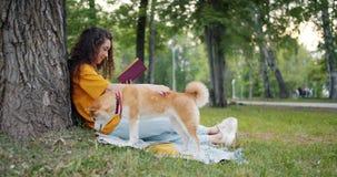 Cámara lenta del libro de lectura del estudiante mientras que su perro que come la hierba en parque en césped metrajes
