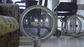 Cámara lenta del manojo de sillas de ruedas con las ruedas blancas puestas al lado de ventanas metrajes