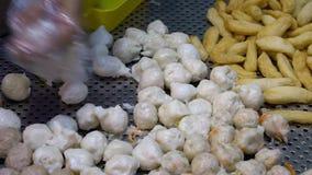 Cámara lenta del manos asiáticas del tendero del tempura tomar las bolas hervidas metrajes