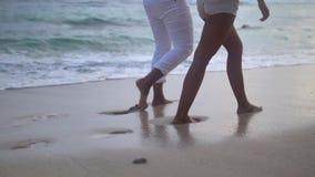 Cámara lenta del paseo de los pares de común acuerdo en la playa, el tiro bajo de la muchacha y las piernas del muchacho almacen de metraje de vídeo