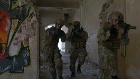 Cámara lenta del pelotón del ejército de las fuerzas especiales que corre y que se separa con las ruinas de un edificio en ejerci almacen de video